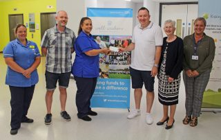 Handing over the cheque to staff from the chemotherapy unit
