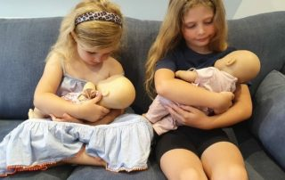 Girls breastfeeding their dolls