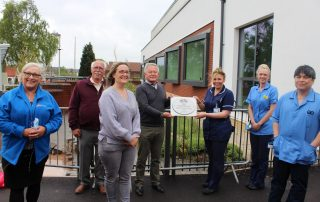 Volunteers hand over the special plaque to critical care staff